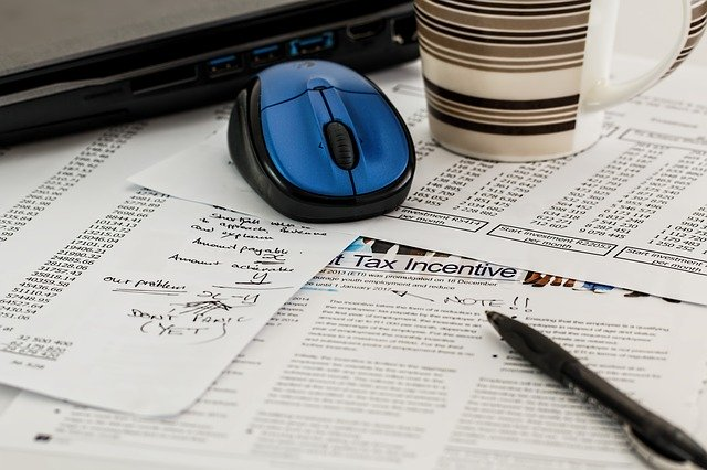 Tax Documents, a Pen, Cup, and Computer Mouse
